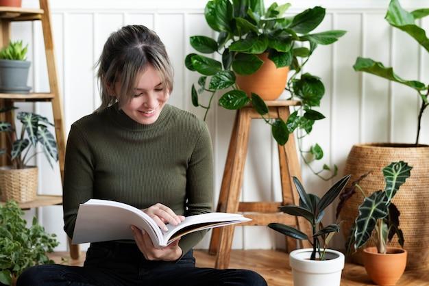 Mujer joven leyendo un libro sobre jardinería rodeado de plantas en macetas