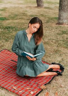 Mujer joven leyendo un libro sobre una manta para picnic