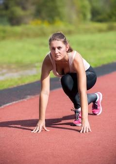 Mujer joven leyendo en la línea de salida para correr