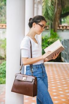 Mujer joven leyendo poesía en un jardín.
