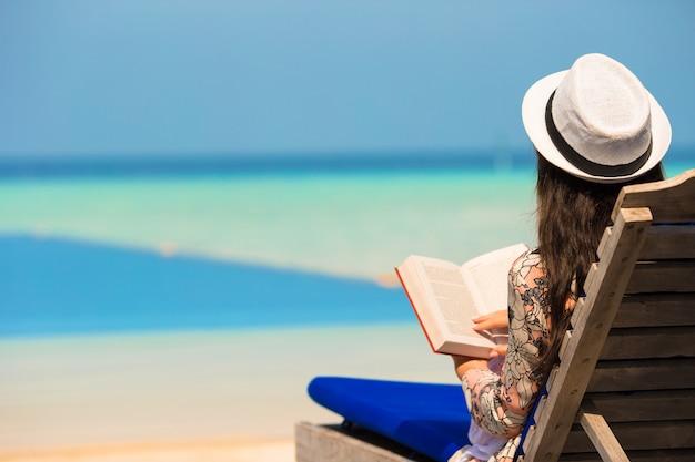 Mujer joven leyó el libro junto a la piscina
