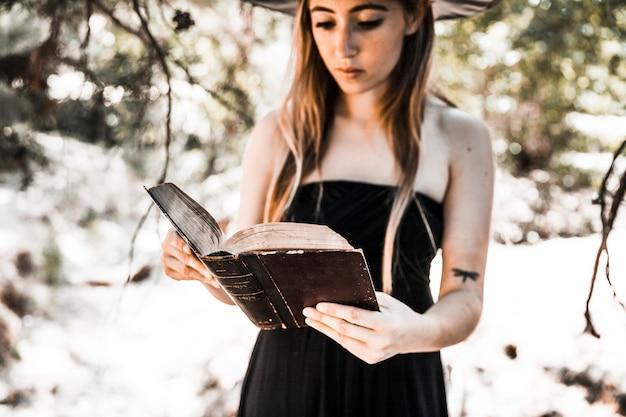Mujer joven en el libro de lectura del sombrero en el bosque