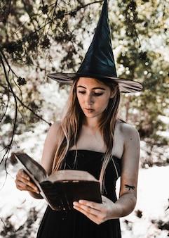 Mujer joven en el libro de lectura del sombrero de bruja en el bosque