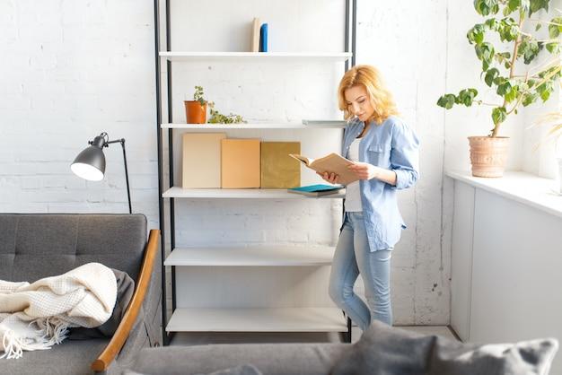 Mujer joven con libro de pie cerca del estante, sala de estar en tonos blancos y sofá acogedor