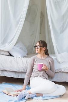 Mujer joven con libro sosteniendo la taza de café mirando a otro lado