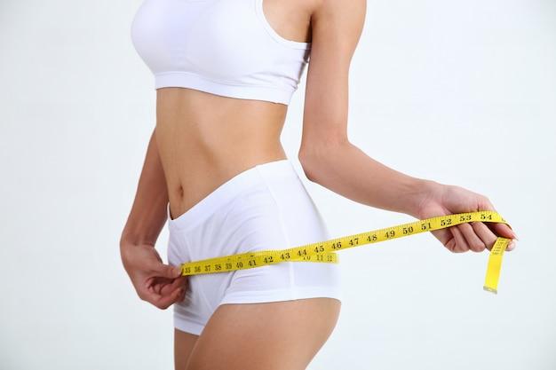 Mujer joven con limo hermoso cuerpo y cinta métrica
