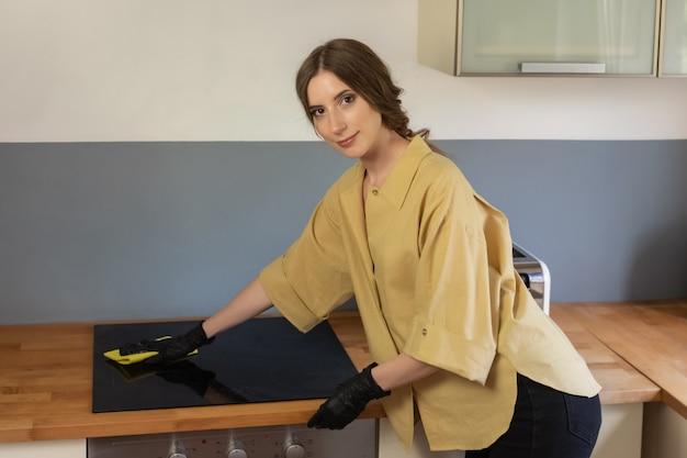 Una mujer joven se limpia en la cocina, lavando platos. está cansada pero contenta de hacerlo.