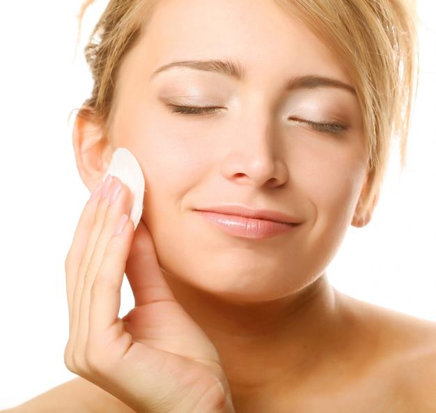 Mujer joven se limpia la piel de la cara