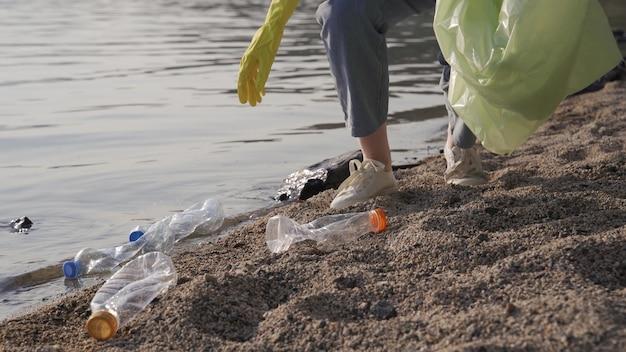 Mujer joven limpia la playa de la basura.