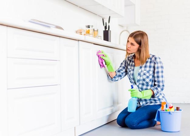 Mujer joven limpiando la casa