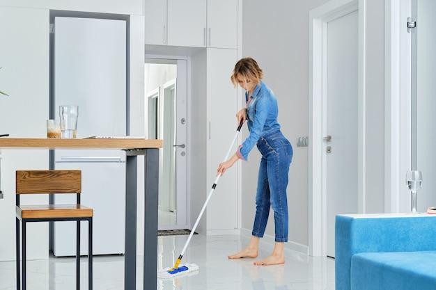 Mujer joven limpiando su piso con un trapeador