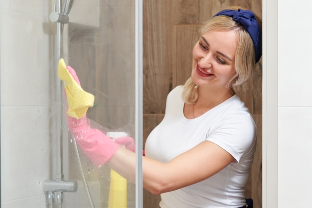 Mujer joven limpieza cabina de ducha de vidrio con esponja y atomizador