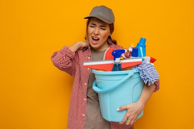 Mujer joven de la limpieza en camisa a cuadros y gorra sosteniendo un balde con herramientas de limpieza con aspecto de malestar tocando su cuello sintiendo dolor de pie sobre fondo naranja