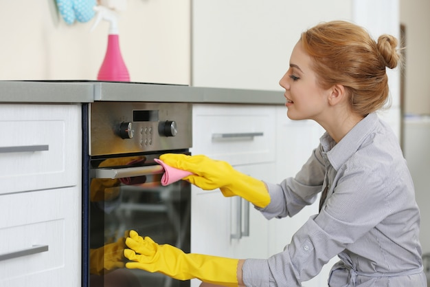 Mujer joven limpieza de horno en la cocina