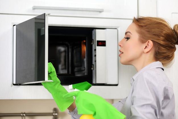 Mujer joven limpieza de microondas con una esponja