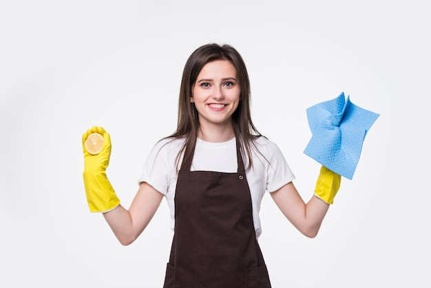 Mujer joven de la limpieza de pie y sosteniendo una esponja contra
