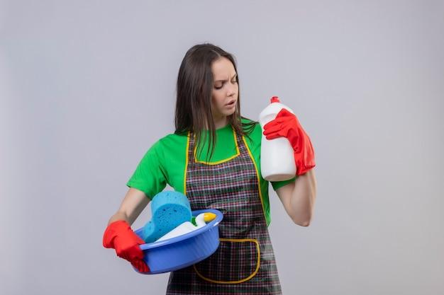 Mujer joven de limpieza con uniforme en guantes rojos sosteniendo herramientas de limpieza y buscando agente de limpieza en su mano en la pared blanca aislada