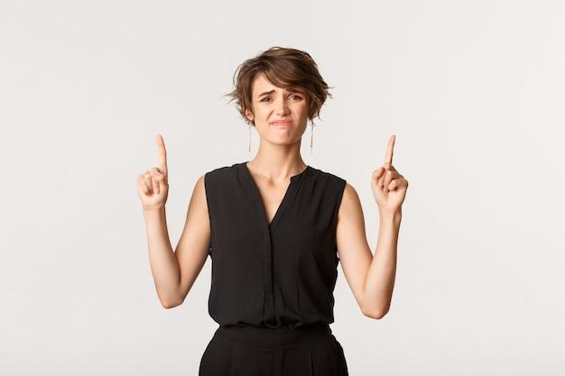 Mujer joven linda dudosa haciendo muecas de disgusto, señalando con el dedo hacia el mal logo, de pie blanco.