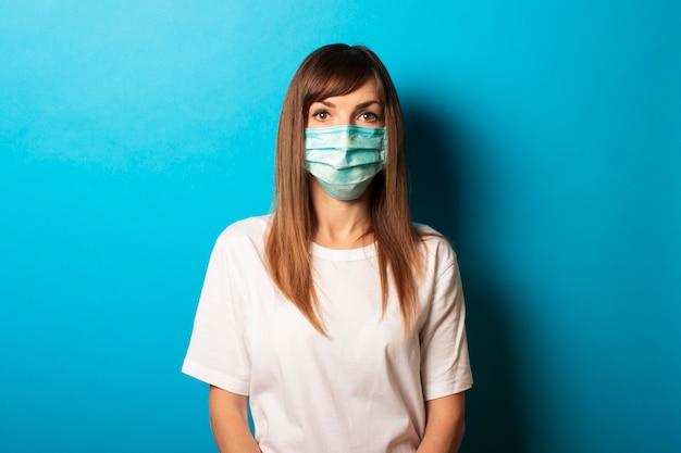 Mujer joven linda en máscara médica protectora y camiseta blanca en azul. concepto de protección personal contra virus, enfermedad, virus, epidemia, pandemia