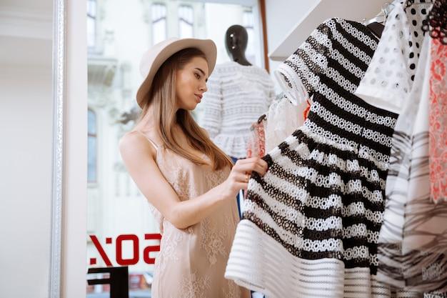 Mujer joven linda pensativa con sombrero haciendo compras en la tienda de ropa