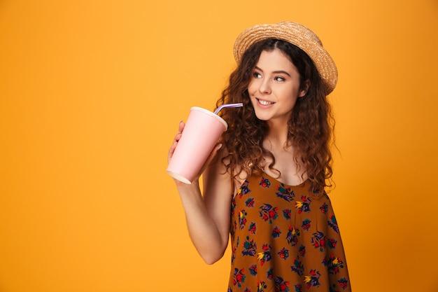 Mujer joven linda que bebe el agua dulce aireada.