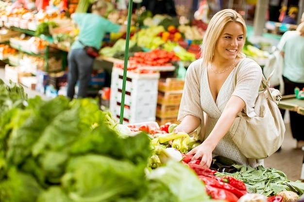 Mujer joven linda que compra verduras en el mercado
