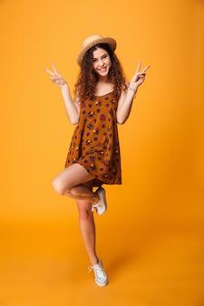 Mujer joven linda que muestra gesto de paz.