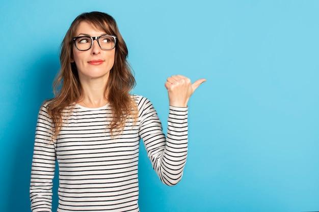 La mujer joven linda que sonríe con los vidrios y un suéter rayado señala su pulgar al lado en azul. cara emocional concepto sorpresa, presta atención