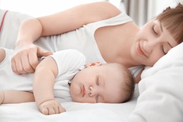 Mujer joven con lindo bebé durmiendo acostado en la cama en casa