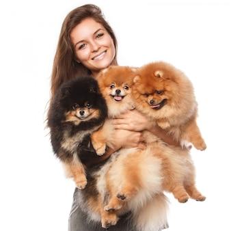 Mujer joven y lindos perros spitz