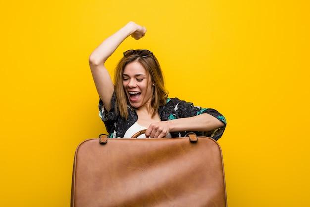 Mujer joven lista para irse de vacaciones sobre fondo amarillo