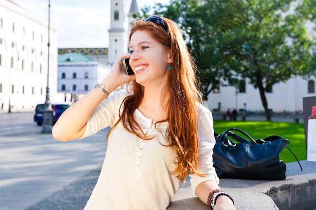 Mujer joven llama con teléfono móvil en el parque