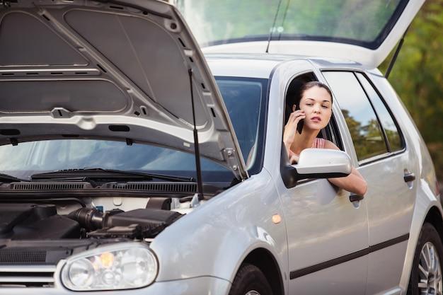 Mujer joven llamando al servicio de evacuación. su auto se descompuso en la carretera.
