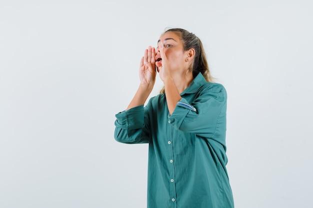 Mujer joven llamando a alguien con voz fuerte en camisa azul y mirando indefenso