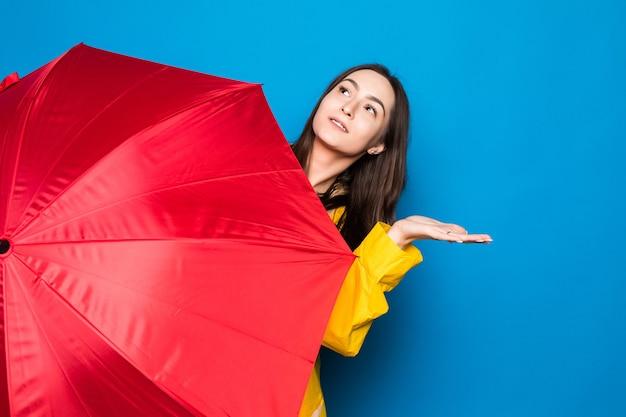 Mujer joven, llevando, capa de lluvia, tenencia, colorido, paraguas, encima, pared azul