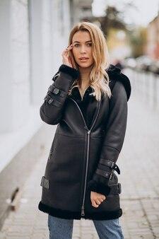 Mujer joven, llevando, chaqueta, ambulante, exterior