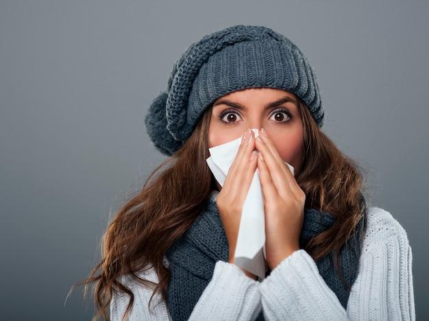 Mujer joven, llevando, gorro calentito, estornudar
