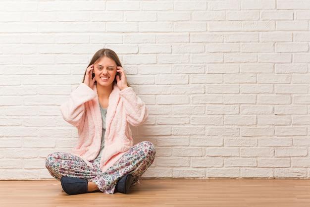 Mujer joven, llevando, pijama, cubierta, orejas, con, manos