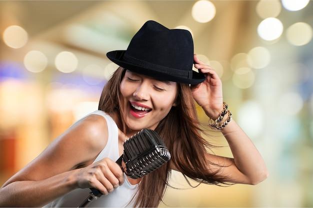 Mujer joven, llevando, sombrero, canto, en, micrófono