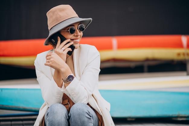 Mujer joven, llevando, sombrero, y, utilizar, teléfono