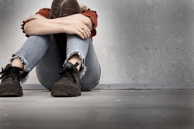 Mujer joven llora y sentada cerca de una pared vacía, sola triste y deprimida niña sosteniendo su cabeza hacia abajo
