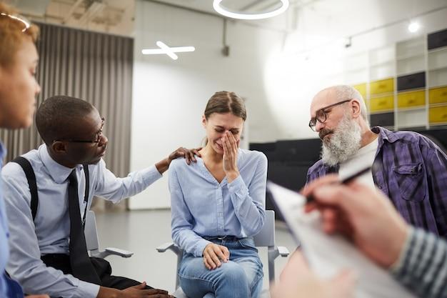 Mujer joven llorando en grupo de apoyo