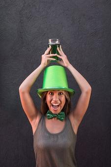 Mujer joven llorando en el sombrero de san patricio con vaso de bebida