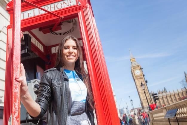 Mujer joven en londres con cabina telefónica y big ben