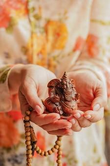 Mujer joven con lord ganesha sclupture en sus manos celebran el festival de ganesha