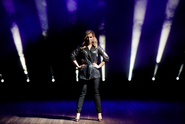 Mujer joven con luces de colores en concierto en el escenario