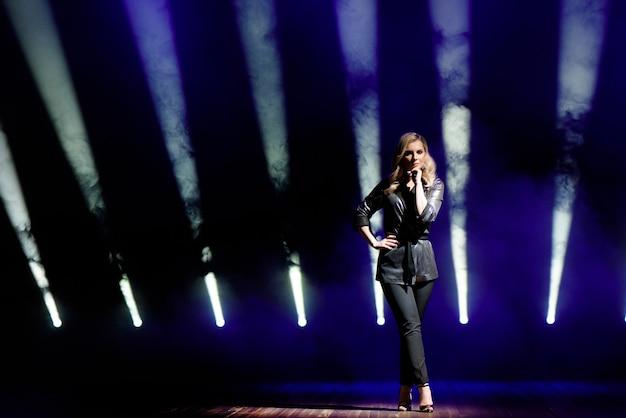 Mujer joven con luces de colores en concierto en el escenario.