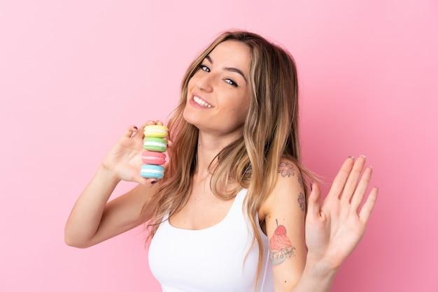 Mujer joven con macarons saludando con la mano con expresión feliz