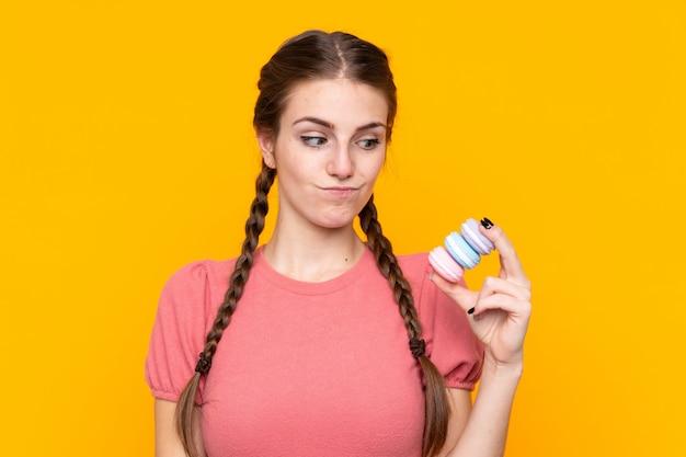 Mujer joven con macarons sobre pared aislada