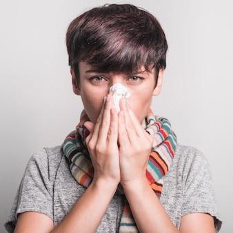 Mujer joven mal que sopla su nariz contra el fondo gris